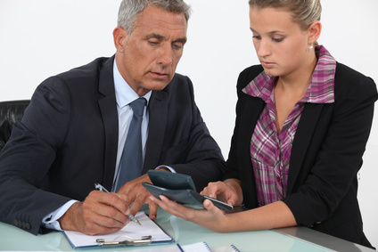 Businessman and woman using a calculator
